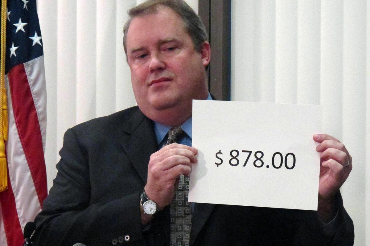 Alaska Revenue Commissioner Bryan Butcher holds up the amount of this year's Permanent Fund Dividend during a news conference Tuesday, Sept. 18, 2012, in Anchorage, Alaska. Butcher announced this year's check from the state's oil riches will be $878 for n