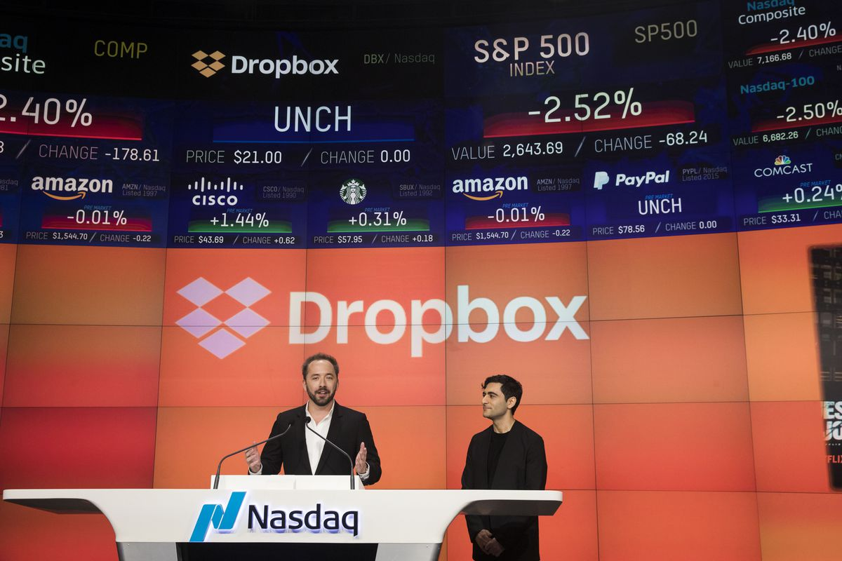 Dropbox CEO Drew Houston and co-founder Arash Ferdowsistand behind a Nasdaq podium at their IPO.