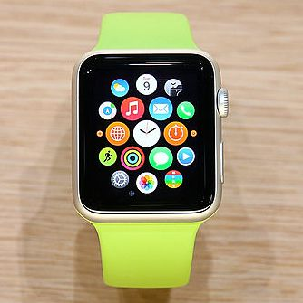 A closeup of the original Apple Watch, with a gaggle of round app buttons clustered around a tiny analog clock-face.