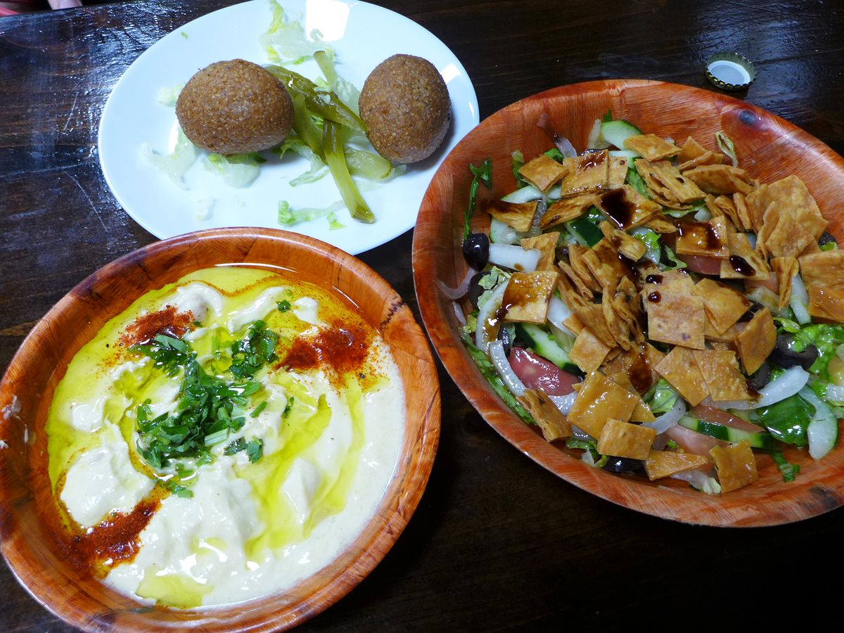 Plates and bowls of kibbe, fattoush, and hummus.