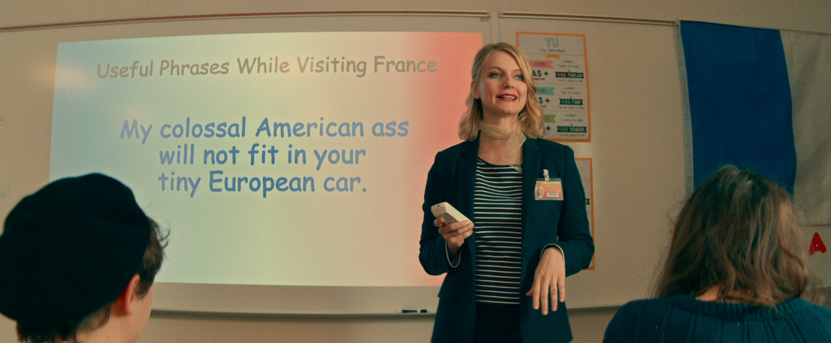 a french teacher in front of a powerpoint slide that says My colossal American ass will not fit into your tiny European car