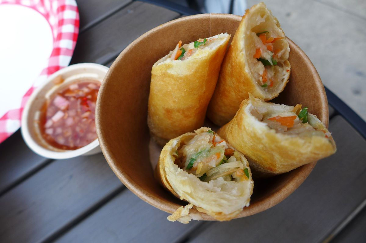 A paper cup with four egg rolls sticking out.