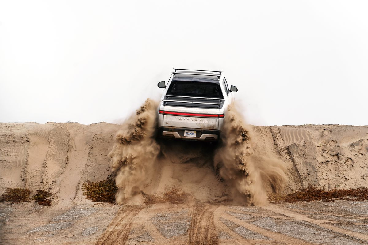 One of Rivian's car models is seen driving away from the camera and over a pile of dirt.