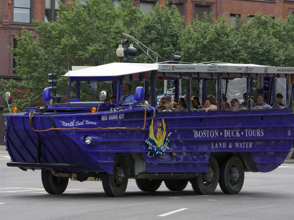 A large blue combination boat and truck rides along a street in Boston.