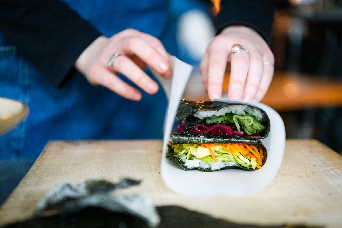 Paper encircles a colorful seaweed wrap filled with carrots, beets, rice, and pickles.