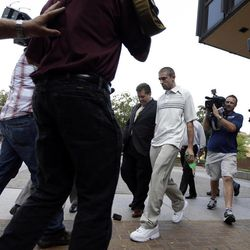 Kenneth W. Smith Jr., center, accompanied by his lawyer Bill Brennan, center left, walks near the U.S. Courthouse, Friday, Sept. 7, 2012, in Philadelphia. Smith was arrested and is charged with making a hoax threat that led authorities to recall a plane in midair to the Philadelphia airport. Federal authorities charged 26-year-old Smith Jr. with conveying false and misleading information. According to a criminal complaint, Smith called police at the airport on Thursday, Sept. 6, 2012 and falsely reported a passenger was carrying an explosive substance. Authorities then recalled a Dallas-bound US Airways flight to Philadelphia.