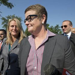 Plaintiffs in the California Proposition 8 case, Kris Perry, center, and her partner Sandy Stier, left, both from Berkeley, Calif., arrive at the Supreme Court in Washington, Tuesday, June 25, 2013, as key decisions are expected to be announced. Other plaintiffs in the case are Jeff Zarrillo, far left. At far right is Chad Griffin,  president of the Human Rights Campaign. (AP Photo/J. Scott Applewhite)
