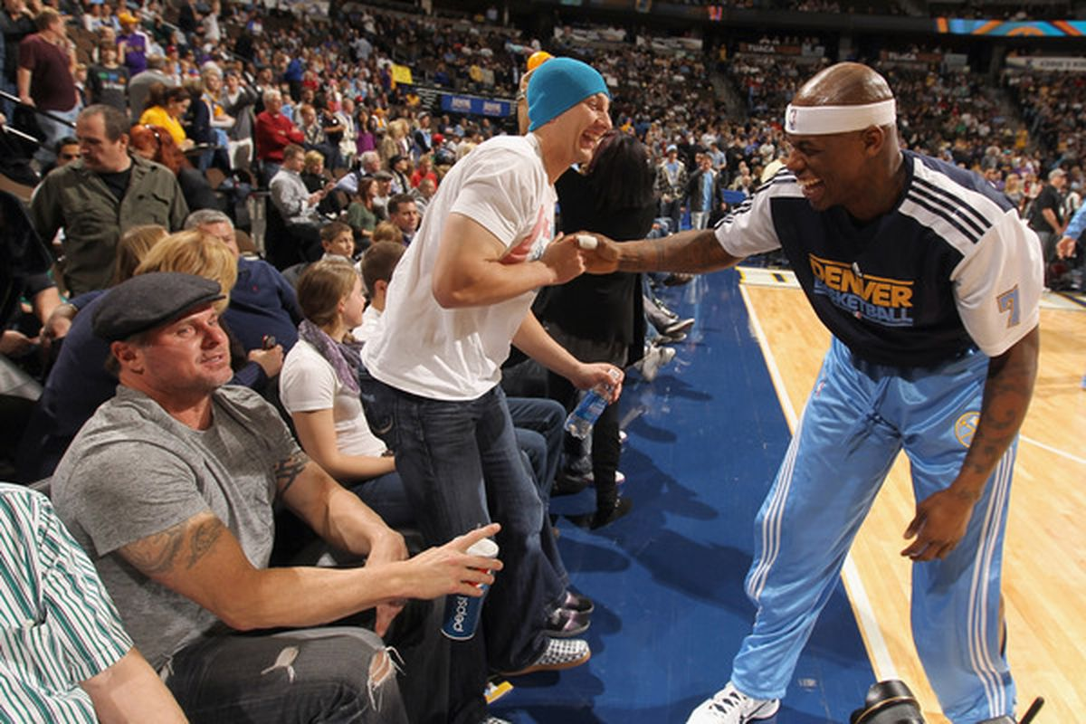 Al Harrington shares some laughs with Troy Tulowitzki and Jason Giambi of the Colorado Rockies as the Nuggets host the Los Angeles Lakers at the Pepsi Center on January 21, 2011.