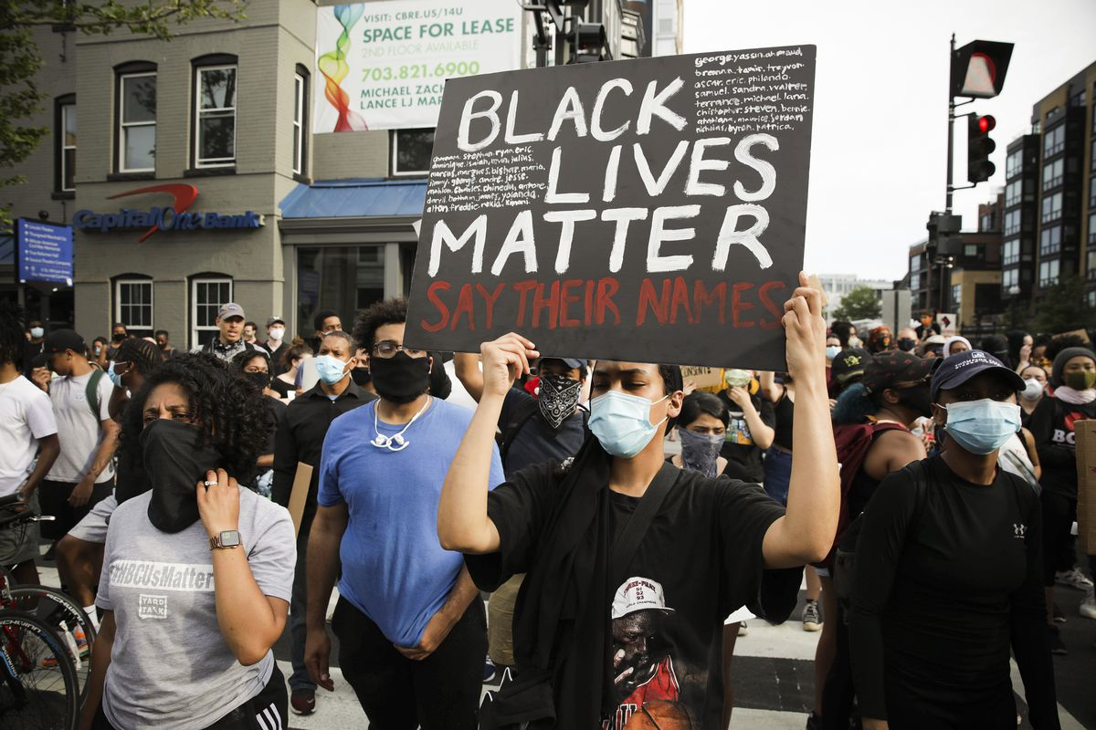 "A dense cluster of protesters, all in masks. in the center is a person in a black t-shirt featuring Michael Jordan. Their sign reads, ""Black Lives Matter Say Their Names."""