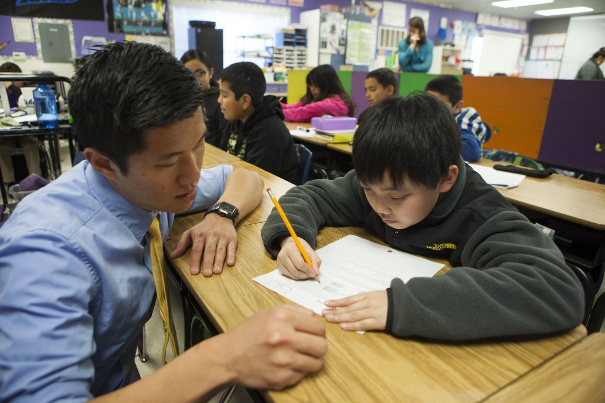 Fifth grade science and math teacher Stephen Pham helps a student at Rocketship SI Se Puede, a charter, public elementary school.