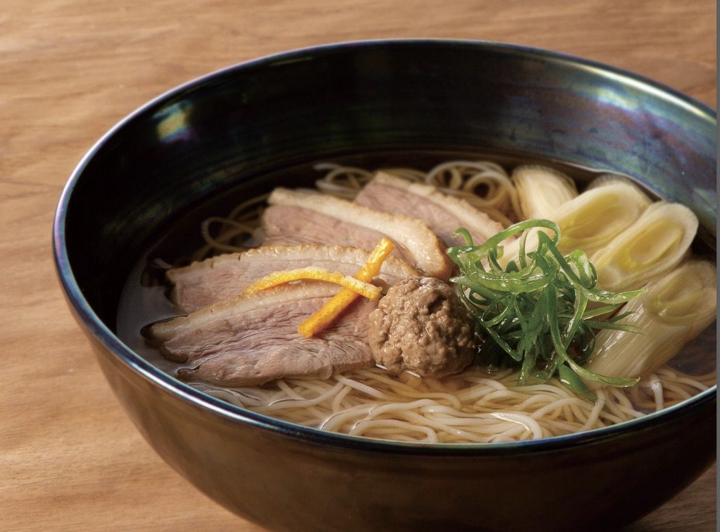 A black bowl filled with soba noodles, duck, and leek