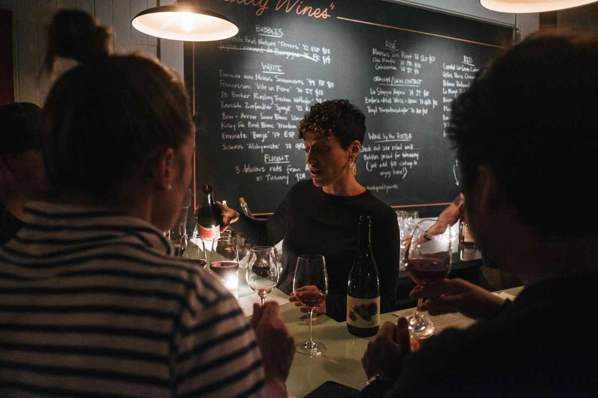 Dana Frank, with short, curly hair and gold dangling earrings, pours wine at Bar Norman. She stands in front of a chalkboard with wines written on it.