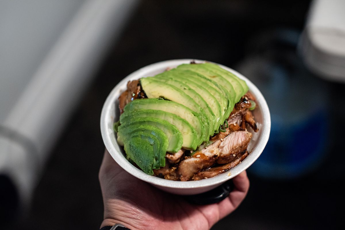 A white bowl with lots of avocado and chicken teriyaki below at a night market.