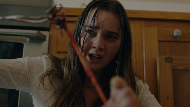The Beach House protagonist Liana Liberato, looking wet and stringy-haired, stares at a bit of stringy gore she appears to be pulling from a body in The Beach House.