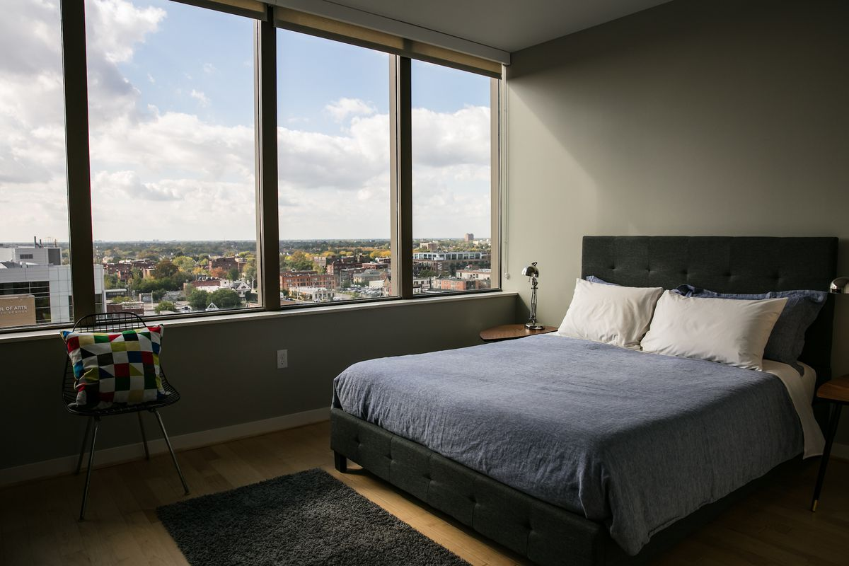 A bedroom with windows overlooking a city.