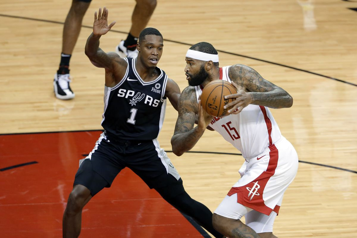 Houston Rockets center DeMarcus Cousins looks to pass under pressure from San Antonio Spurs guard Lonnie Walker IV during the first half.
