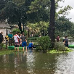 """A dozen LDS Church volunteers — including some donning the yellow """"Mormon Helping Hands"""" jerseys — use kayaks and canoes to evacuate the Robert A. Boyd family and belongings from their flooded Spring, Texas, home on Monday, Aug. 28, 2017."""