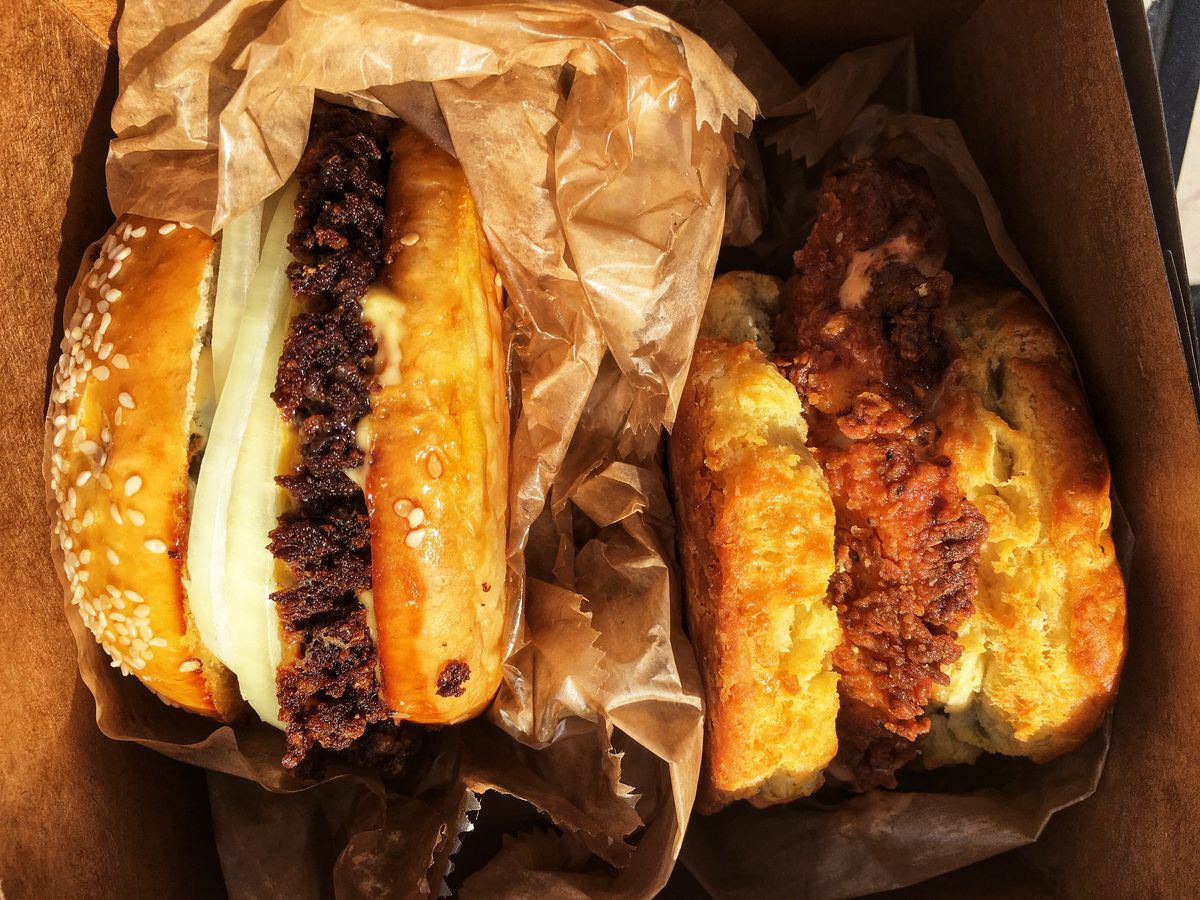 A burger with a crisped edge and a fried chicken and biscuit sandwich in a box.