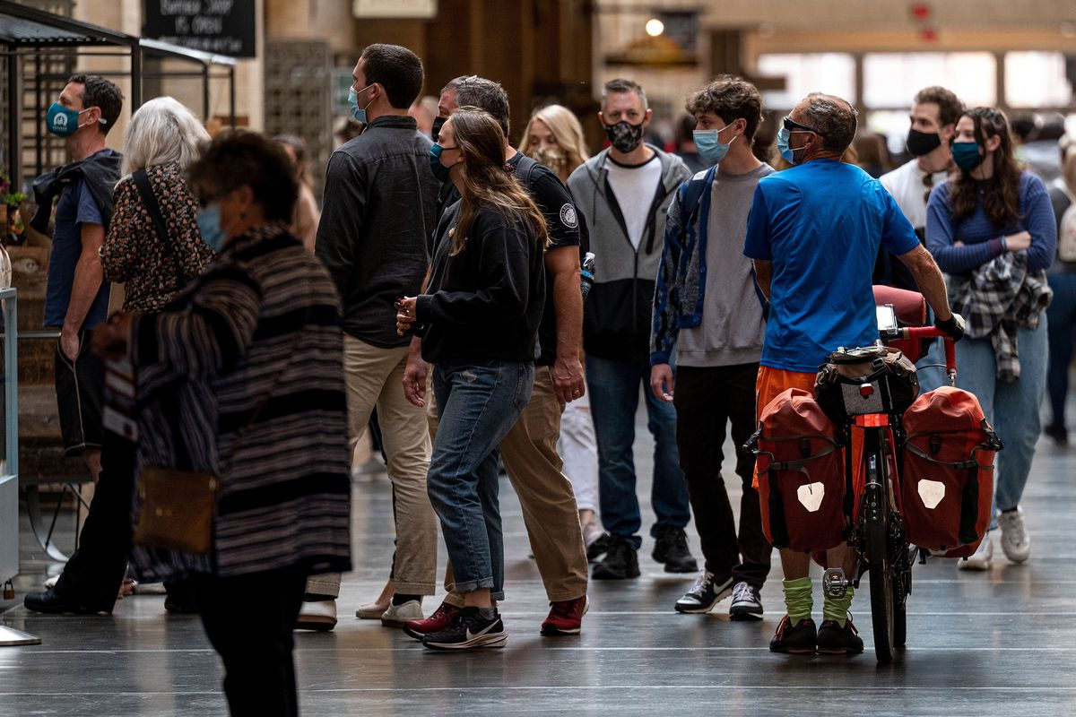 Visitors to the Ferry Building in San Francisco wear masks as they walk around indoors.