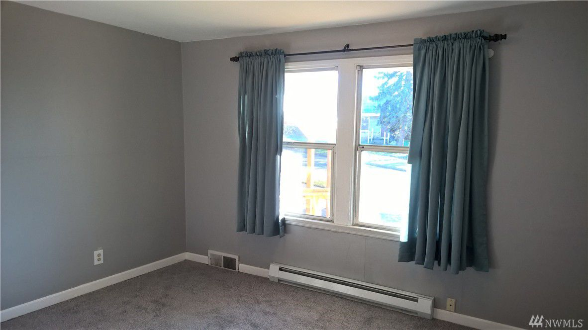A gray bedroom with a curtained window