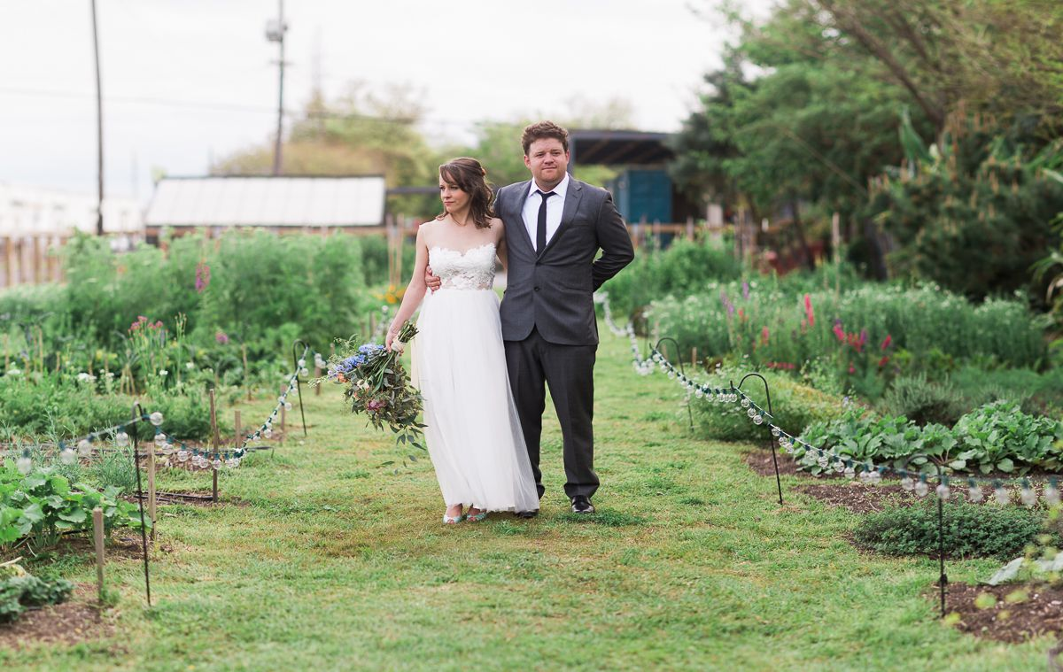A bride in a wedding dress and a groom in a suit stand on a grassy path between two rows of plants at Press Street Gardens in New Orleans.