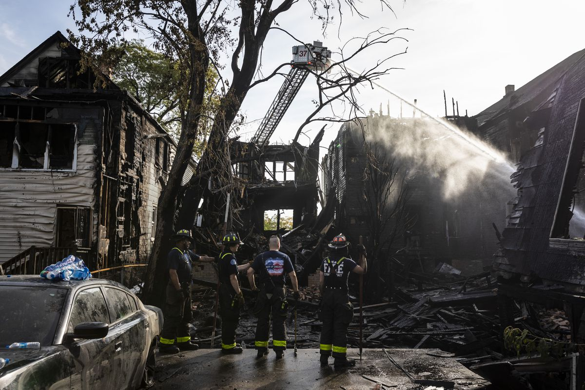 Chicago Fire Department firefighters work to extinguish hot spots Thursday morning after an overnight fire broke out in a vacant building and spread to six other buildings, including two coach houses, in the 4900 block of South Princeton Avenue in Fuller Park on the South Side.