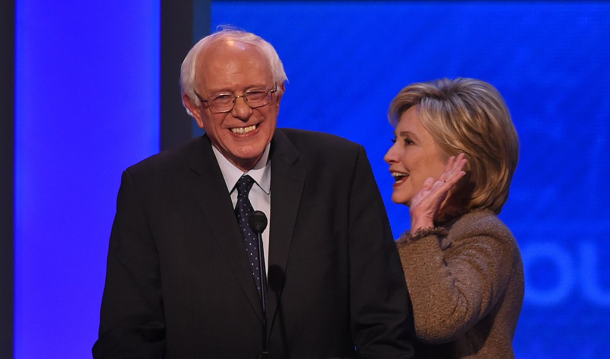 Hillary Clinton and Bernie Sanders, together on stage. She appears to be about to pat him on the back.