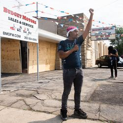 """Reginald Nash Jr. holds hist fist up Tuesday afternoon, Aug. 25, 2020, after a night of unrest following the shooting of Jacob Blake by a police officer in Kenosha Sunday. """"It's so terrifying you can't even go outside your house anymore and not feel threatened by police. … We don't want to damage our cities … We just want to be heard,"""" Nash said."""