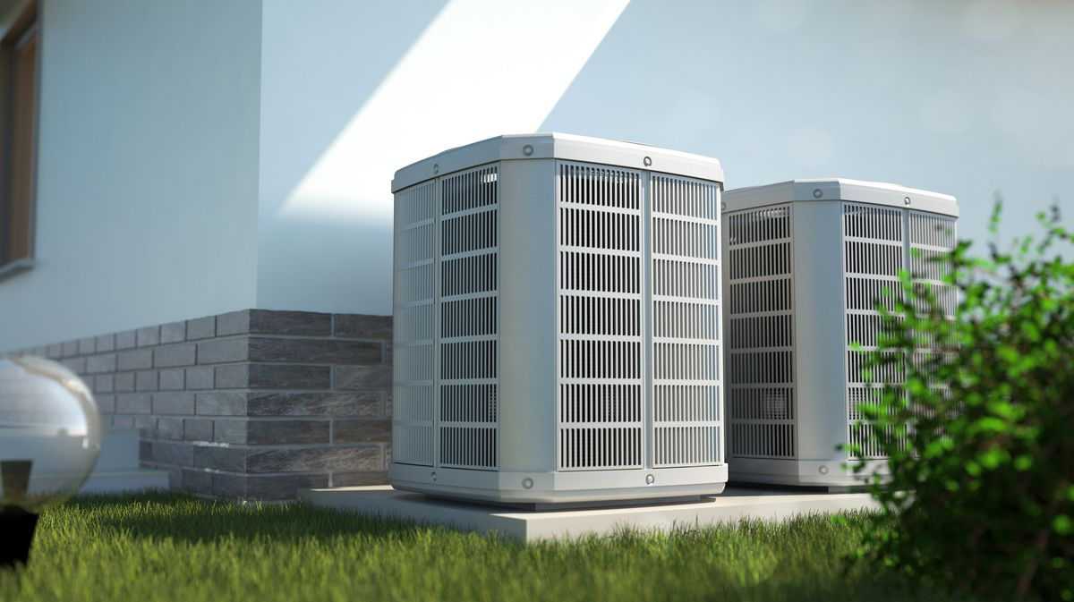 Two central AC units on the exterior of a home with a low grey brick wall and green grass