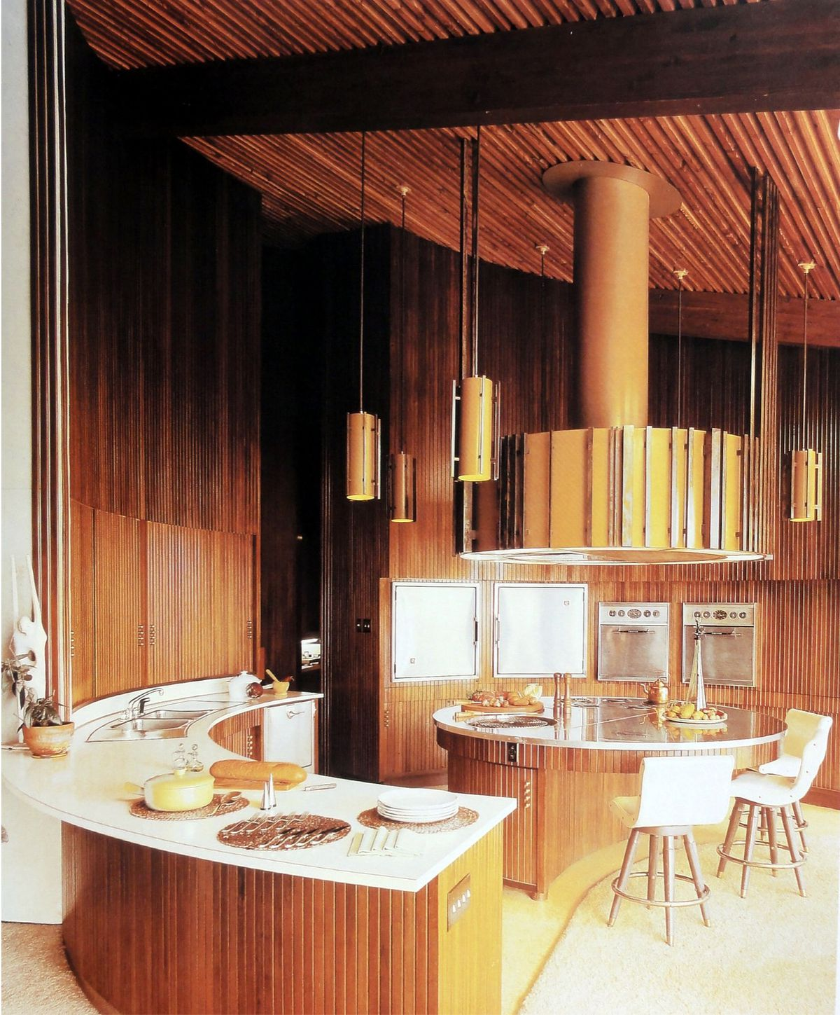 Archival photo showing the kitchen with warm wood walls.