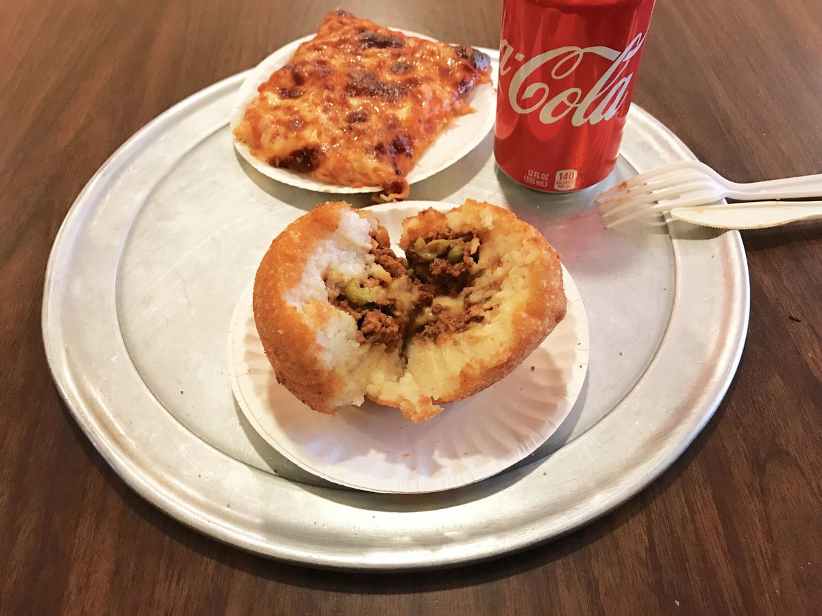A slice of cheese pizza and an open arancino, stuffed with rice, cheese, beef, and peas, at Galleria Umberto North End