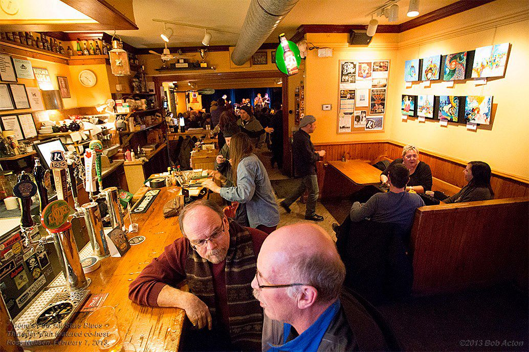A rustic pub with customers sitting at a bar and in a booth.