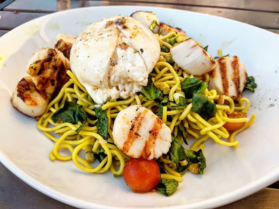 A pile of yellow noodles is topped with grilled scallops and a large portion of burrata, served on a white plate on a wooden picnic table.