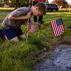 Volunteer Tate Cocciniglio, 11, places a flag at a marker at Larkin Sunset Gardens Cemetery in Sandy on Thursday, May 27, 2021. More than 200 youth volunteers from around the Salt Lake Valley honored military veterans for Memorial Day by placing 3,000 American flags on the graves of service members. In addition, they swept and polished headstones and helped beautify cemetery grounds.