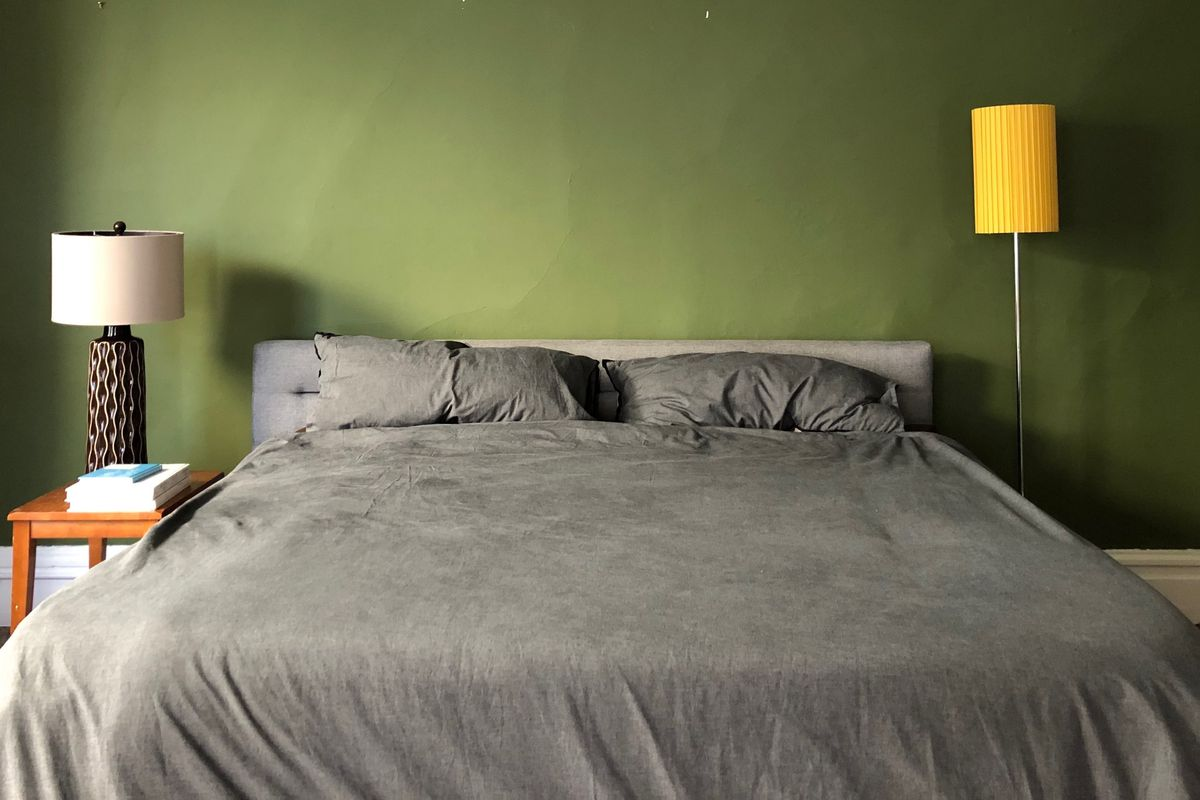 A large bed with gray duvet, a dark green wall, a wooden nightstand with a lamp and three books.