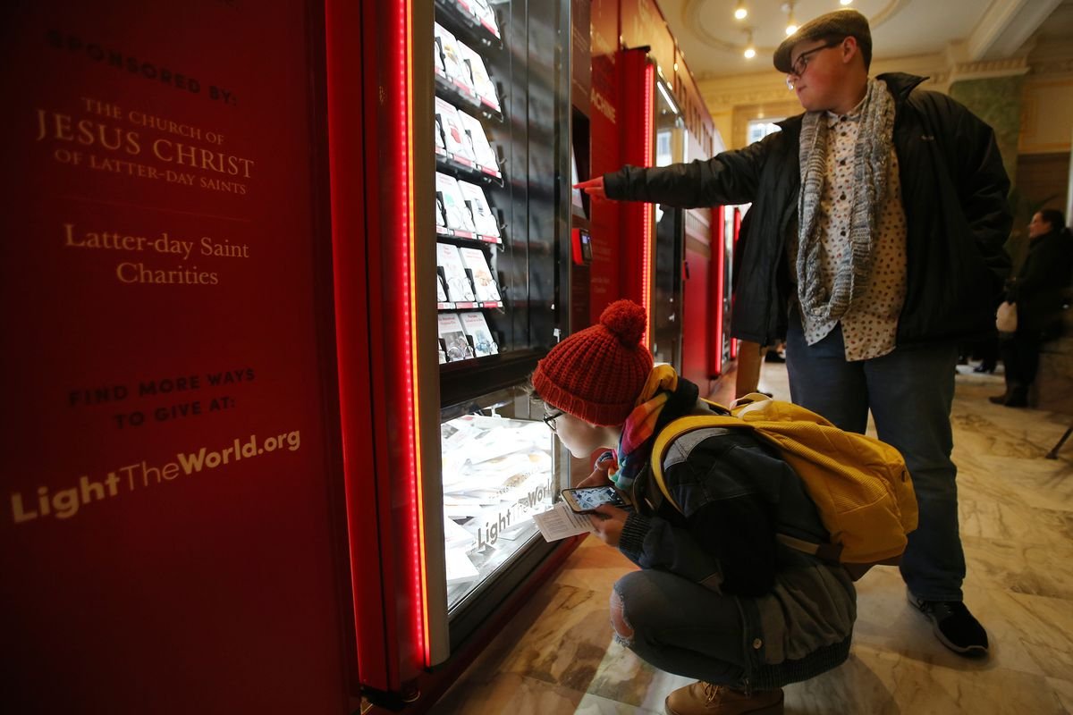 Kessa Woolsey and her brother, James Woolsey, look at items that can be donated in a #LightTheWorld Giving Machine in the lobby of the Joseph Smith Memorial Building in Salt Lake City on Monday, Nov. 25, 2019. The machines are one way people can become involved in The Church of Jesus Christ of Latter-day Saints' #LightTheWorld initiative this December. The machines can be found in 10 cities around the world.