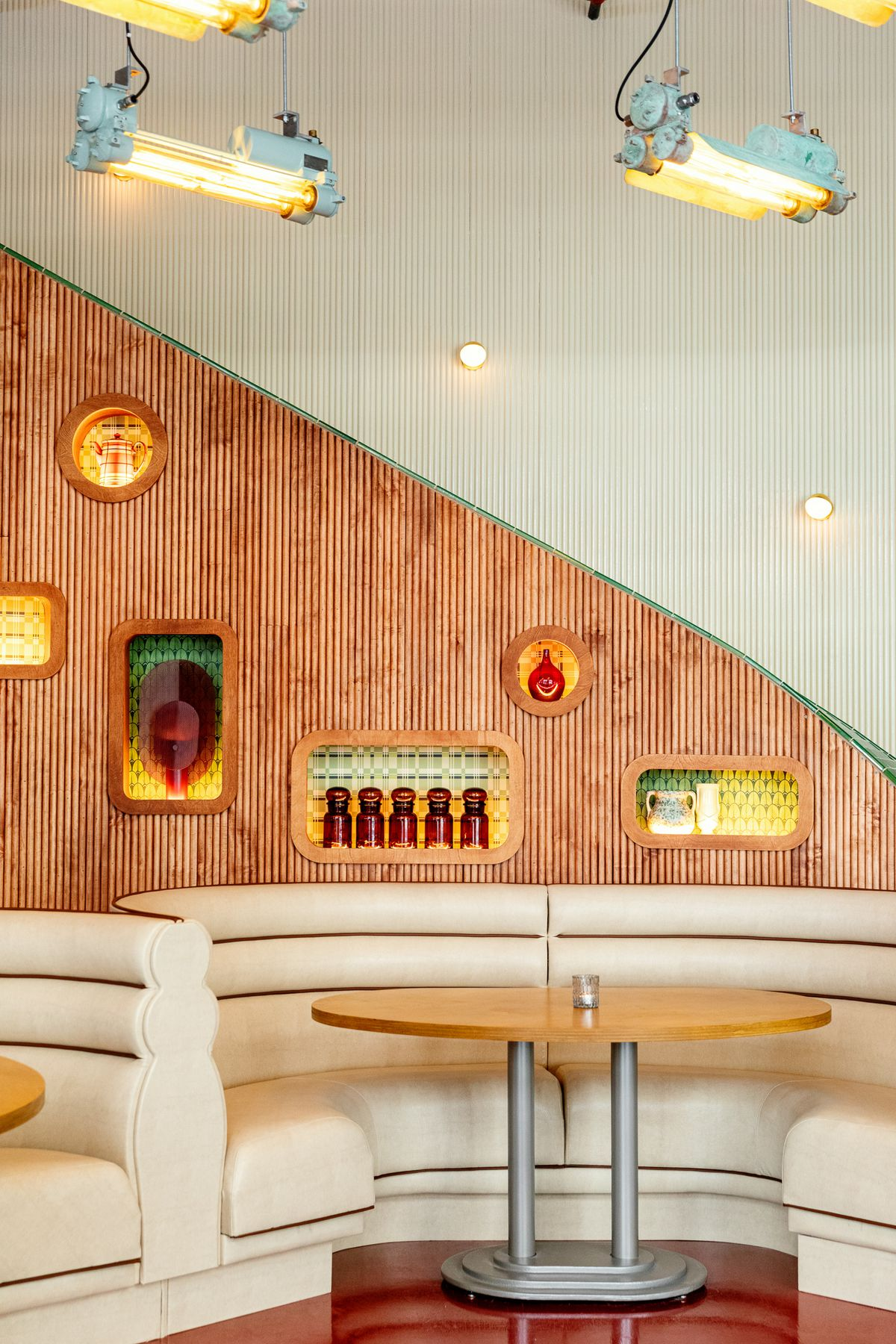 Two leather dining booths with a backdrop of art pieces within cubbies in the wall.
