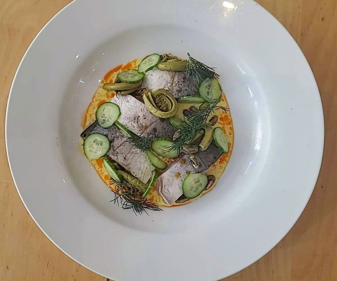 white dish with fiddleheads, fish, and dill