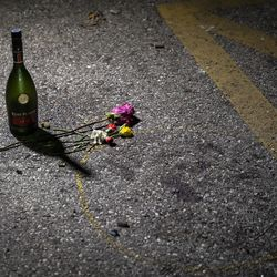Mourners and protesters places flowers and other momentos near a blood stain at the corner of 63rd Street and Sheridan Road, where a person was shot by an alleged vigilante on the fourth day of civil unrest after police shot Jacob Blake, Wednesday night, Aug. 26, 2020. Two people were killed and one person was shot and wounded during unrest Tuesday night and Kyle Rittenhouse, 17, has been charged in connection with the shootings.