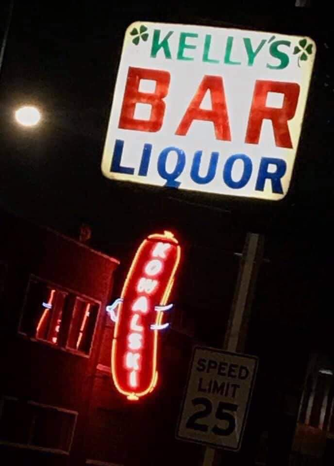 A sign for Kelly's Bar lights the night, juxtaposed with the neon Kowalski sign in the background