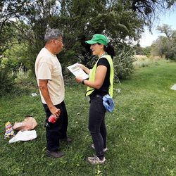 Susan Collier, of Salt Lake City Community Emergency Response Teams, hands a flier to Jesse Yapias in Salt Lake City on Monday, July 18, 2016, warning of possible toxic algae contamination in the Jordan River.