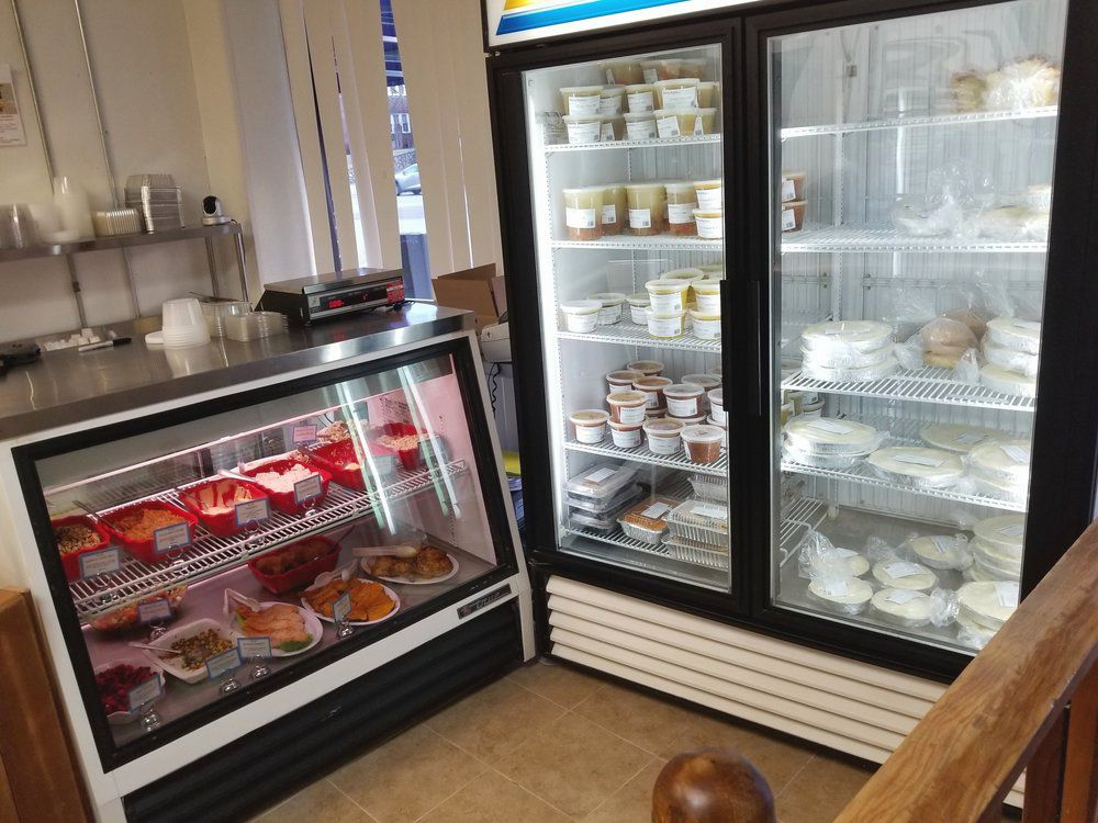 Two fridges — one low an d horizontal, the other tall and vertical — sit in a shop, packed with cakes and other baked goods.