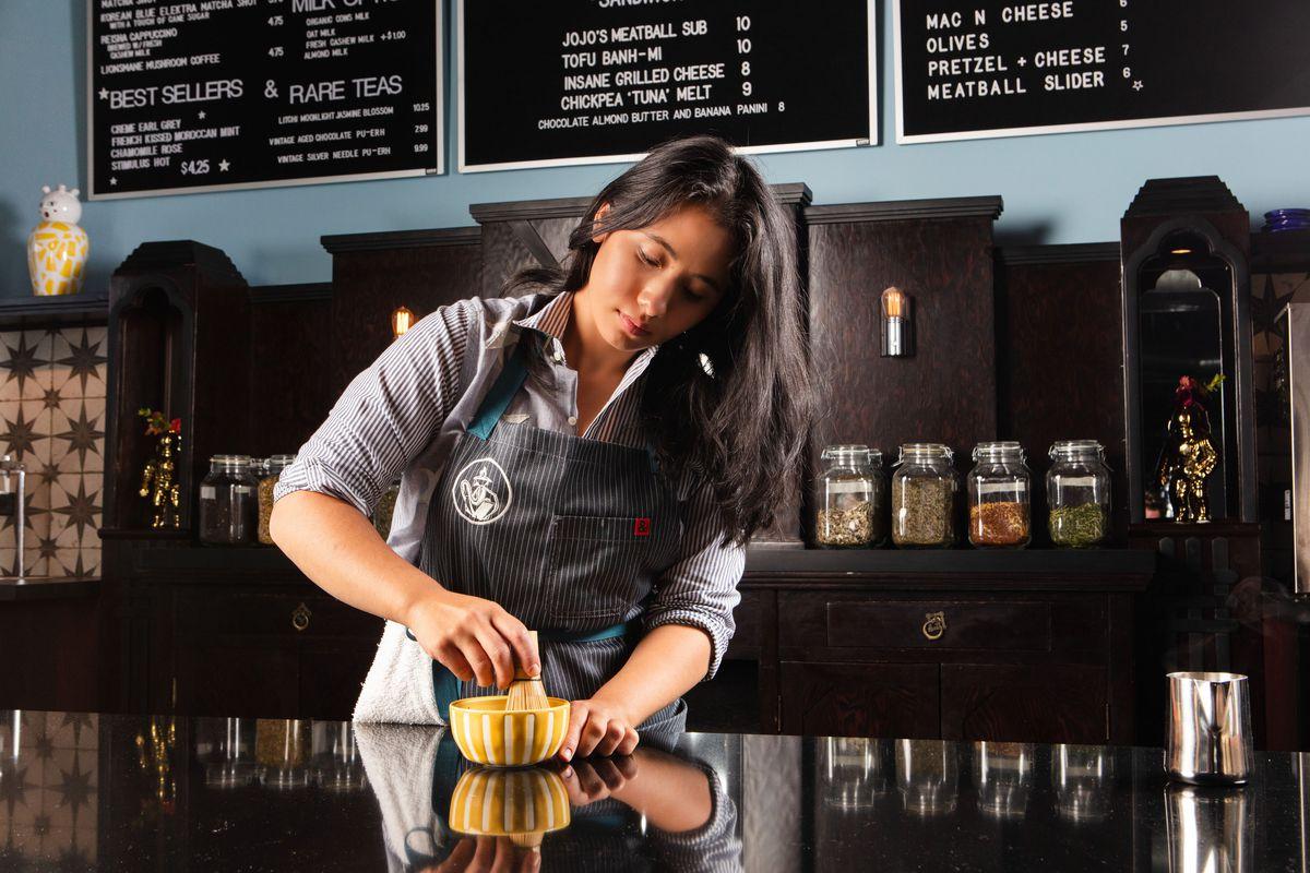 A barista makes tea in a mortar and pestle.