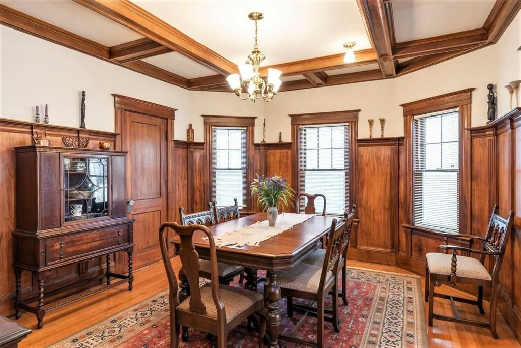 A dining room with wood-beamed ceilings and a table with chairs.