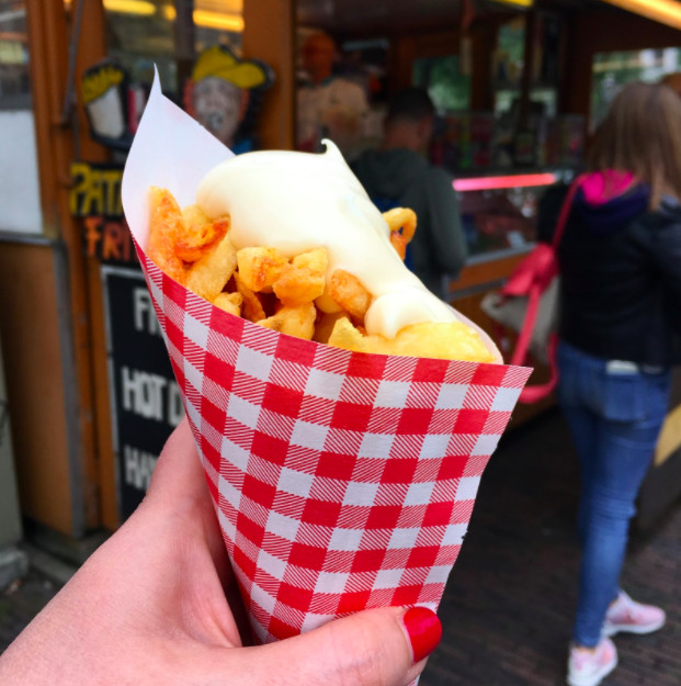 A hand holds a paper cone full of french fries topped with a large dollop of mayonnaise