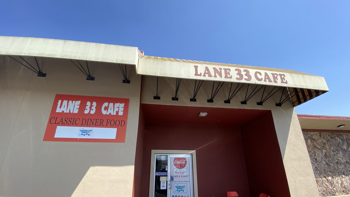The beige exterior and red door of Lane 33 Cafe in Napa