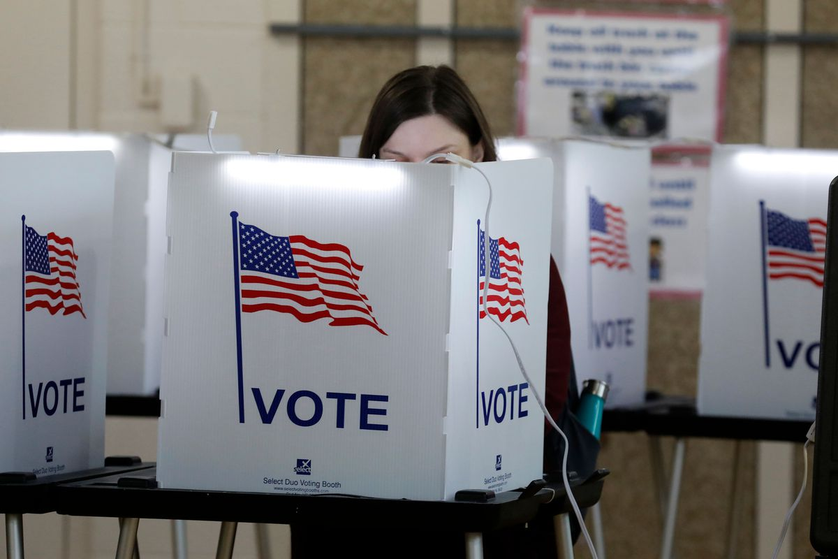 """A person voting behind a desktop screen with a US flag and the word """"vote."""""""