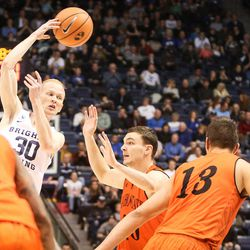 Brigham Young Cougars guard TJ Haws (30) offloads a no-look pass over Idaho State Bengals center Novak Topalovic (13) and guard Balint Moscan (20) in the first half as BYU takes on Idaho State at the Marriott Center in Provo on Thursday, Dec. 21, 2017.