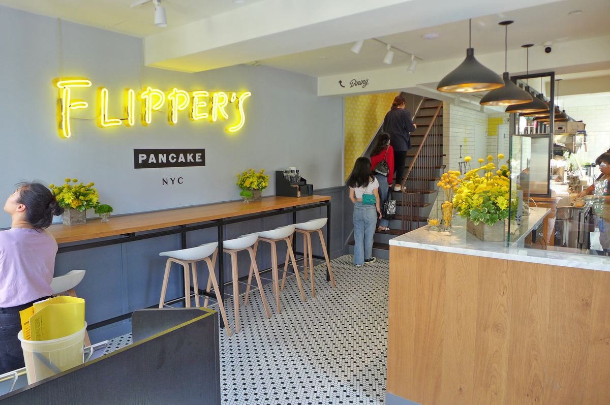 A yellow neon Flipper's sign is seen over a dining counter on the ground floor, with three people traipsing up the stairs at the end of the room to the upstairs dining room...
