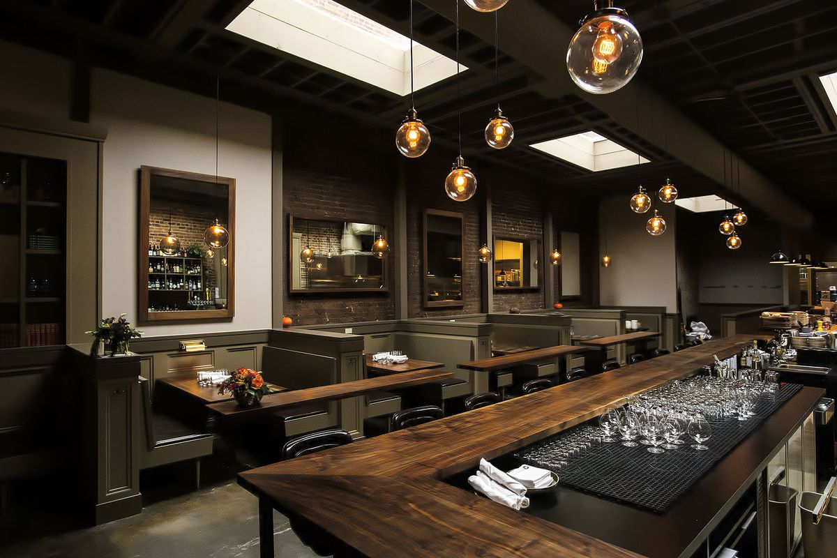 The interior of Bramling Cross, with dark wood accents and a large wraparound bar.